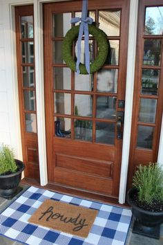 Cute porch all spruced up for spring! Love the blue gingham touches with the moss wreath- HELLO SPRING!