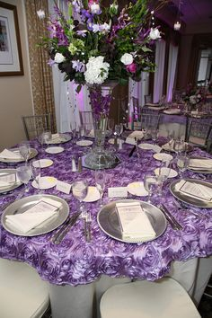 This Centerpiece was made with green and white Hydrangeas, Liatris, Bells of Ireland Purple Freesia, Purple Dendrobium Orchids, Vanda Orchids, Pink Garden Roses. This sits on top of a container with a Vanda submerged in water flowersfromus.net