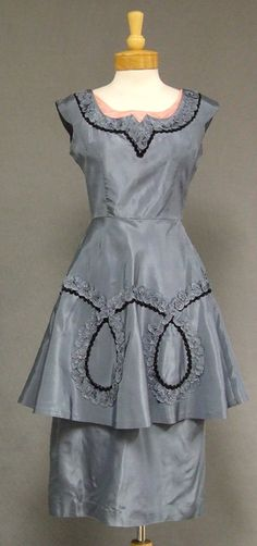 From Vintageous. A stylish and sexy 1950's cocktail dress in slate blue taffeta with self fabric ruffle trim and metallic black braid. Fitted, sleeveless bodice with pink velvet inset at the neckline. Dress has a great double skirt (fitted undernetah and fuller on top.