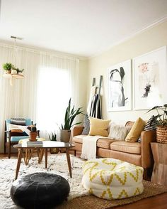 Family and living room: Quilt ladder Rugs and hide layered Classic cognac sofa Plants, large artwork, white curtains Textiles (pillows and pouf)
