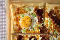 Rezept für eine Blätterteig-Tarte die mit Cheddar Käse, mit Spiegeleiern mit kross gebratenem Bacon und mit Frühlingszwiebeln belegt wird. Der Speck wird vorab in der Pfanne gebraten, damit er schön kross wird.