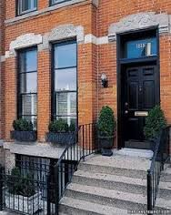 Black painted front door on brick house. Decorative lintels with horizontal stone band. Transom with house numbers. Home Tours: Home Tour: Row House - Martha Stewart Black Window Trims, Black Doors, Brick Building, Red Bricks, Facade House, House Numbers, House Front, Architecture Details, Curb Appeal