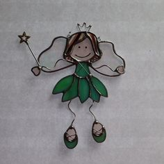This cute little stained glass fairy princess suncatcher is made of hand cut glass. The pieces are individually wrapped in copper foil, and soldered. It comes ready to hang, and measures approximately 6 inches tall x 4 1/2 inches wide. The crown, arms, legs, dress and shoe details, and wand are hand crafted with copper tinned wire. The face is hand painted. The solder is waxed and buffed to shine. This suncatcher will look great in any window. It can also be used as a wall decoration or…