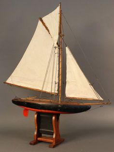 Gaff rigged pond yacht rigged with a suit of three linen sails. Varnished deck with painted hull. Wood cradle. 31 x 6 x 35