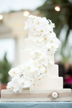 White cake with white orchids cascading a symmetrical down the side, perfect for a seaside or beach wedding