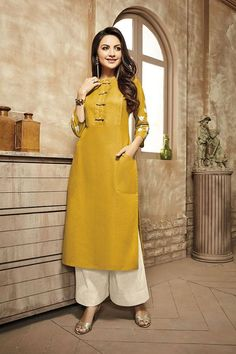 Go classy with this plain yellow designer suit falling plain with self patterning at the Torso with fancy buttons and a pocket at one side of flare in a genteel Outlook! Comes with contrasting cream self worked palazzo pants.This suit is not accompanied by matching dupatta.
