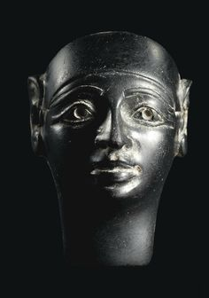 A PHOENICIAN BLACK OBSIDIAN HEAD OF A DIVINITY   CIRCA EARLY 1ST MILLENNIUM B.C.   Probably an inlay, in Egyptianising style, wearing a close-fitting cap, the face with full lips, aquiline nose, almond-shaped eyes with recessed pupils, finely delineated cosmetic lines and contoured eyebrows