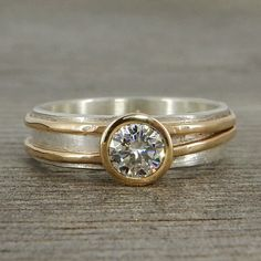 A beautiful 5mm (equivalent to a 0.5 carat diamond) moissanite sits in a 14k gold bezel on a 5mm wide layered 14k yellow gold and sterling silver band. This is a design that can work really well as a wedding ring, or for any other occasion. All of the metal used in this piece is from recycled sources. This is truly a piece you can feel good about wearing, knowing that its creation did not exploit workers or harm the environment. This design is highly customizable - I can use a different…