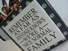 REMEMBER - As Far As Anyone Knows We're A Nice, Normal Family - vinyl saying on wood block with berries on top. $10.00, via Etsy.
