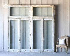 Vintage Windows Large scale vintage French doors with a hinged transom in layers of distressed tan, rust, ivory and grey paint. Back side is similar but also has Kelly green trim. The original hardware is a wonderful historic touch on these lovely doors. We have two available.