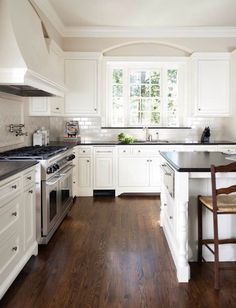 white kitchen with black countertops & dark hardwood floors