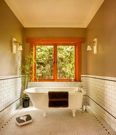 """The master-bath """"tub room"""" includes a restored 1931 Stanley clawfoot bathtub. Walls are an earthy taupe."""