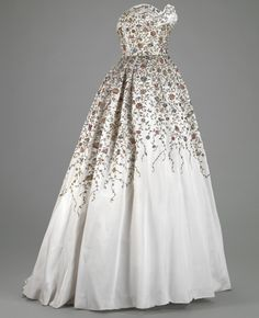 Ball Gown  Pierre Balmain  Autumn/Winter 1953-1954  The ball gown is exquisitely hand-embroidered in a custom, Islamic-inspired floral motif with meandering vines. The boned fitted strapless bodice has a draped sweetheart neckline. Multiple tulle crinolines and a custom hooped petticoat were worn with this dress.  #Ball Gown #Pierre Balmain #Autumn/Winter 1953-1954 ×