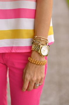 If you ever wanted to pull off hot pink pants, here's how to do it! A thin silk shirt balances the brightness of the pants, while gold-tone accessories add interest to the look, without fighting for attention.