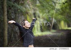 兵庫県武田尾廃線跡のハイキングコースで目をつぶり伸びをする笑顔の若い女性