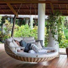 Závěsná houpací ratanová pohovka na verandě