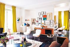 Modern living space with yellow curtains, gallery wall, and cool furniture