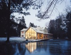 The Floating Farmhouse's semitransparent addition has a roofline that matches the pitch of the original 1820s farmhouse. A porch, tucked under the side eaves, is cantilevered over a stream that runs through the property. Ikea loungers are illuminated from the interior by commercial gymnasium lights repurposed as pendant lamps.  Photo by: Mark Mahaney      Read more: http://www.dwell.com/slideshows/hope-floats.html#ixzz2678O9wpJ