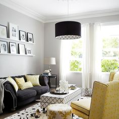 Yellow and black living room features a black drum pendant illuminating stacked shelves lined with black and white family photos placed above a black roll arm sofa with silver nailhead trim accented with a gray throw blanket and yellow pillows facing a black and white trellis ottoman as coffee table.