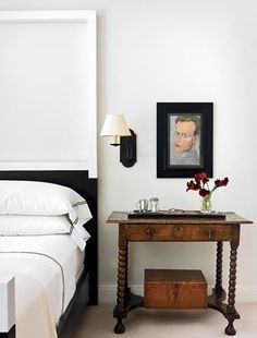 In the master bedroom, Handman paired traditional end tables with a Christian Liaigre bed, which has a dark rift-sawn oak base and white-lacquered tops on the footboard and tall headboard.
