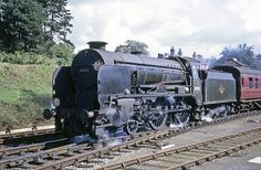 An old Schools Class 4-4-0 pulls slowly out of New Milton with a an inter-regional service for Bournemouth in the summer of 1961. These locomotives were given the names of famous elite schools in southern England. This engine is 30934 'St Lawrence'. Hampshire, England. Transparency scan.