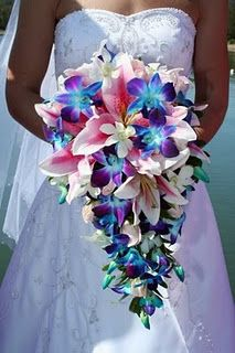 Beautiful Lilies and White and blue orchids in a cascading bouquet.