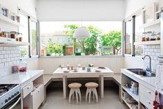 Cocina comedor integrados en casa en un country. Un gran ventanal aporta luz y conecta con el exterior. En las paredes de la cocina, azulejo tipo subway neoyorquino.