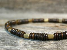 Ox bone heishi dyed to a dark brown is beaded with ethiopian brass faceted tube beads. Dark rich color with gold brass look great together and beaded on strong stretch cord. Wear this one alone or with other bracelets...great piece for adding some rich color.  Size: Choose from the drop down menu above right. These beads are a smaller 4-5mm size. See the last picture for a comparison size.  This bone is dyed and should not be exposed to any bleach or paint thinner or any kind of harsh…