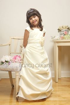 Satin Flower Girl Dress with Ruched Skirt: Your little princess will dazzle in this long satin flower girl dress. No matter what the occasion, this gorgeous flower girl dress will be positively perfect! This particular dress is made entirely of satin with a classic bodice, a pleated wide waistband and the most amazing skirt. The floor length skirt features beautiful ruching that drapes from side to side. The skirt is further enhanced with a slight built in crinoline for a little extra…