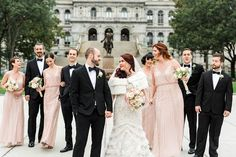 A formal wedding party with bridesmaids in blush dresses and groomsmen in black tuxedos.