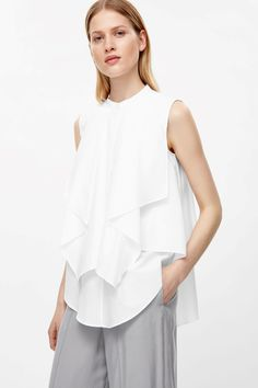 Designed with draped layers, this sleeveless blouse is made from a soft cotton a subtle brushed texture. An A-line fit, it has a hidden half placket, an asymmetrical hemline and a round neckline with a single button fastening.