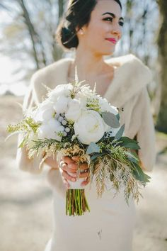 This winter bride looks gorgeous in her cropped  fur jacket, and the traditional white bouquet dressed up with   wintry   greenery just tops off the look.