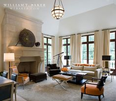 William T. Baker | coffee table, curtains, french door, globe pendant light, mantel, orange chair, sofa, tall ceilings