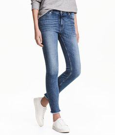 Denim blue. 5-pocket, slim-fit, ankle-length jeans in washed superstretch denim with distressed details. Regular waist, zip fly with button, and raw, frayed