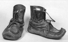 Sko Ett par skidpjäxor, kallas även näbbkängor, av läder. Läderrem och svart vävt ylleband att knytas kring vristen.