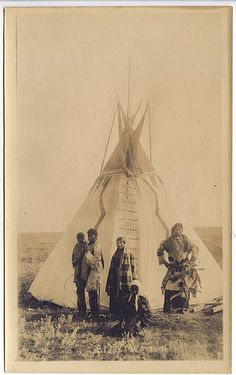 SIOUX FAMILY POSED BEFORE THEIR PAINTED TIPI.