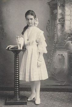 Girl standing, with her cat on a stand.