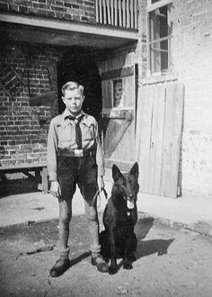 Hitler Youth boy with large black German Shepherd.