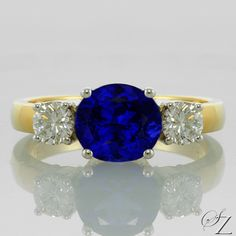 A mesmerizing deep blue Tanzanite between shimmering white Diamond brilliants set in white gold claws with a contrasting yellow gold band. Absolutely gorgeous!