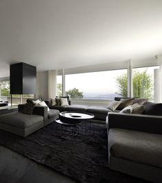 Living room in Suisse by Iria Degen Interiors. Grey tones and lots of different textures.