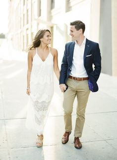 Female wearing long lace dress and male wearing white and tan with a sport jacket.
