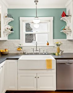 I love the white cabinets and clean subway tile next to the pretty aqua paint color (Benjamin Moore Kensington Green #710). Love the sink too!