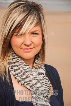 Female model with Blonde hair highlights wearing blue top and striped scarf against beach background stock photo