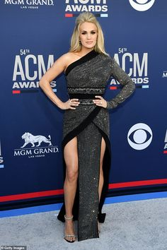 Carrie Underwood dazzled in a black sequin gown while walking the red carpet at the 2019 American Country Music Awards, arm in arm with her husband Mike Fisher, three months after birth. Floral Print Gowns, Printed Gowns, Black Sequin Gown, Black Sequins, Carrie Underwood, American Country Music Awards, Lace Sleeves, Dresses With Sleeves, Sexy Gown