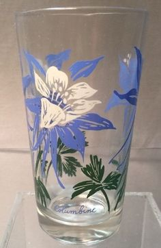 """This tumbler has the blue """"Columbine"""" written at the bottom in script with a fancy """"e."""" The flower is blue with a white interior and green leaves. This fun retro piece is in nice condition for its age, with no chips or cracks.   eBay!"""