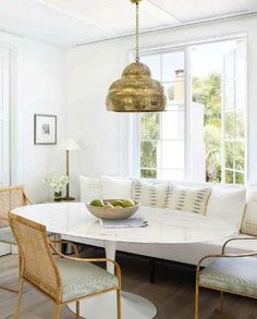 chic breakfast room with white bench seat under the window, gold Moroccan style pendant light, woven cane chairs, white walls: