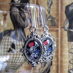 Victorian ornamental metal frames with a glass dome cabochon featuring altered art images of the white rabbit from Alice in Wonderland. Handy lockable kidney earrings wires. The earring measures 25 x 39 mm.