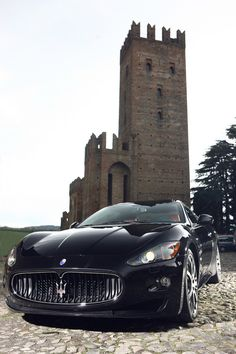A car as grand and imposing as the structure behind it: the 2013 Maserati GranTurismo S. #Maserati #MaseratiGranTurismo #MaseratiGranTurismoS