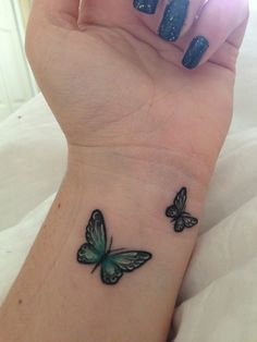 Two small butterfly tattoos on girls wrist