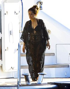 Stylish cover-up: She later donned a semi-sheer black kaftan, but her enviable physique wa...